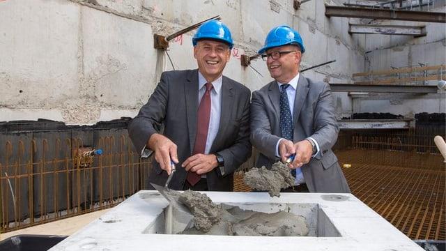 Baudirektro Hanspeter Wessels und Kunstmuseums-Direktor Bernhard Mendes Bürgi mit blauem Helm und Mauererkelle.