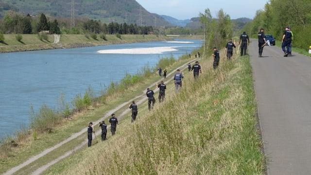 Polizisten am Rheinufer auf der Suche nach Spuren.
