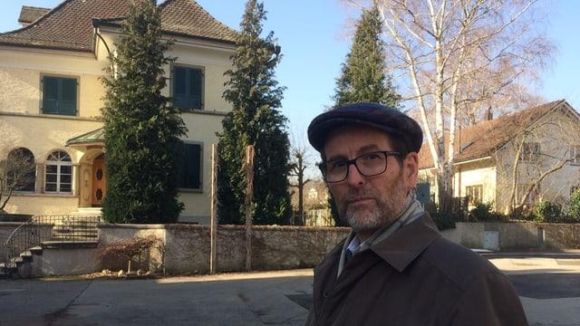 Mann mit Hut vor Villa.