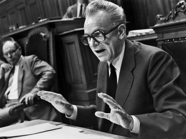 Leon Schlumpf in einer schwarzweissen Fotografie. Er sitzt im Parlament und trägt eine markante Brille