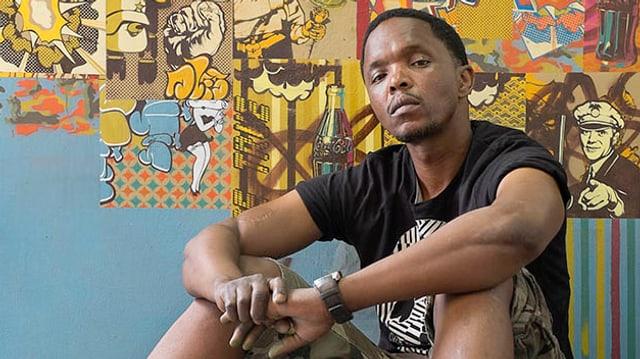 Ein afrikanischer Mann sitzt auf dem Boden vor einer Wand voller Collagen und schaut ernst in die Kamera.