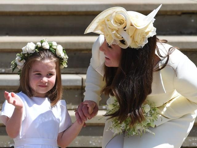 Mädchen mit Blumenkranz im Haar und Mutter mit Hut