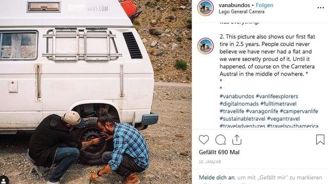 Zwei Männer hantieren am platten Reifen eines weissen VW-Bus.