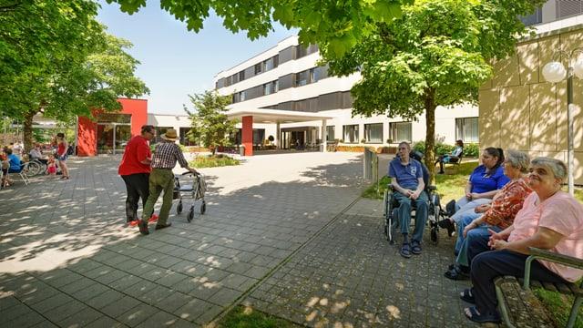 Gebäude im Hintergrund, davor Menschen am Rollator und im Rollstuhl.