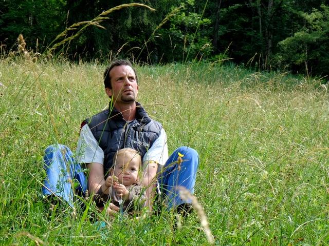 Franco Bösch sitzt in einer Wiese, seine Tochter im Arm.