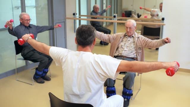 Ältere Menschen trainieren mit Hanteln.