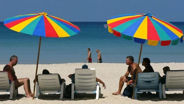Persunas che fan vacanzas sper la mar.