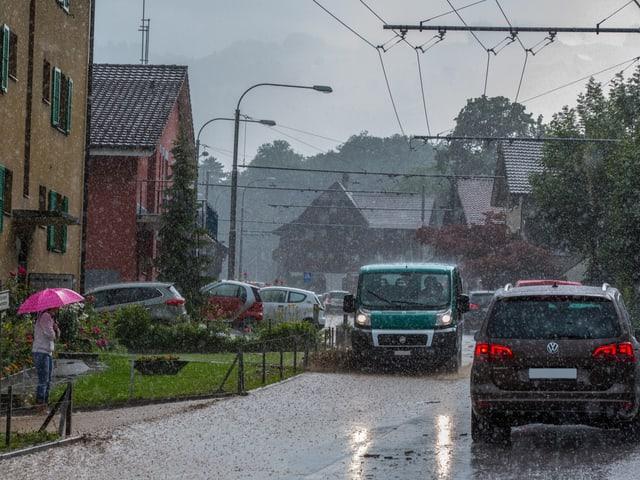 Von braunem Wasser überflutete Strasse. Es regnet weiter, Autos versuchen zu fahren, eine Frau mit einem rosa Regenschirm kämpft sich auf dem Gehweg durch das Unwetter.