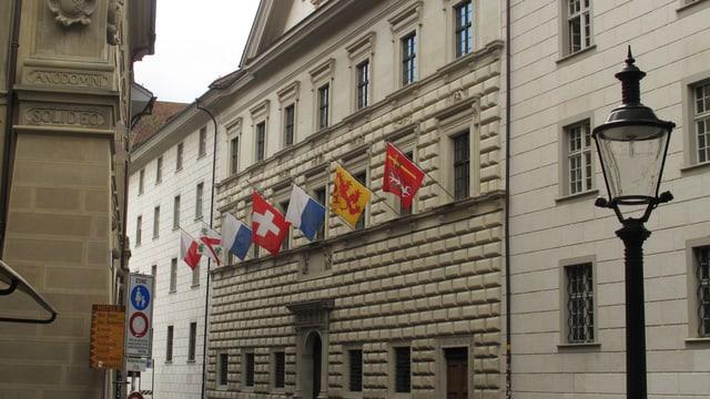Ein graues Gebäude, daran hängen die Fahnen der Luzerner Gemeinden.