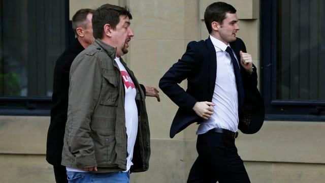 Der Angeklagte rennt in den Gerichtssaal, um den Kameras zu entkommen.