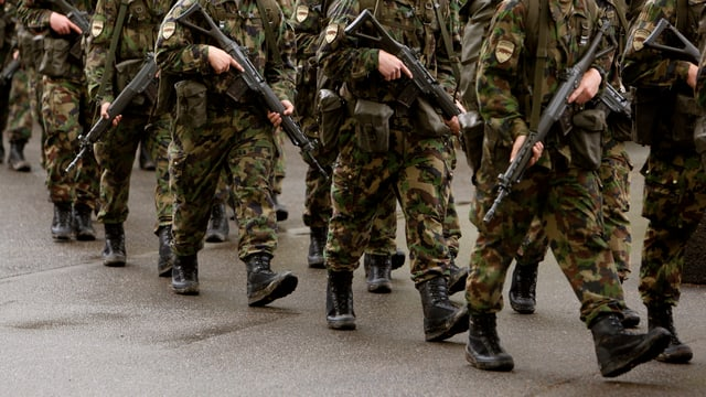 Soldaten gehen hintereinander die Strasse entlang.