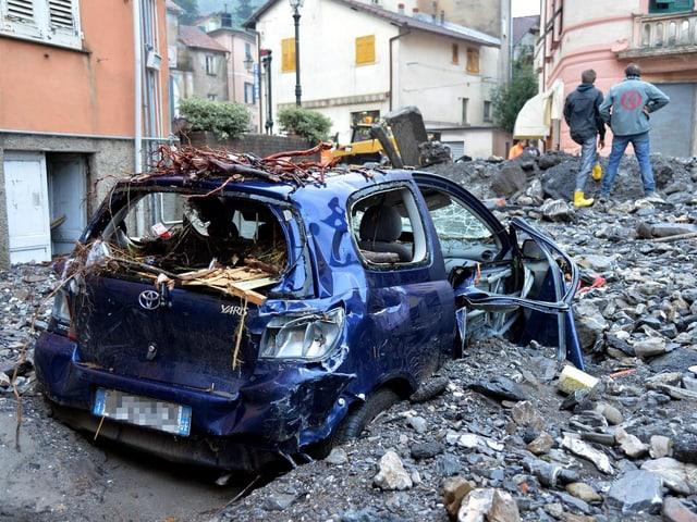 Ein demoliertes Auto steht inmitten von Gestein und Geröll, das sich in einer Strasse angehäuft hat.