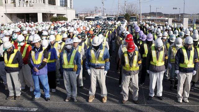Lavurers a Fukushima che lavuran per la decontaminaziun dal terren fan ina minuta da silenzi