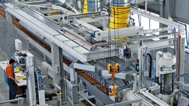 Ein Arbeiter in einer grossen Industriehalle der Alu Menziken AG.