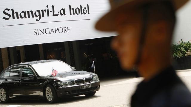 Ein Wachmann steht vor dem Shangri-La Hotel in Singapur. Ein Wagen der US-Delegation steht davor.