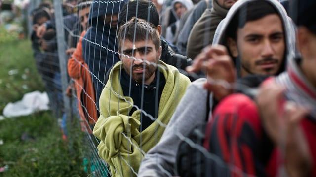 Flüchtlinge an einem Grenzzaun.