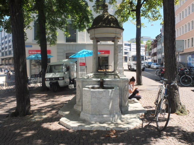 Steinerner Brunnen mit einer kleinen Kuppel über dem Hahnen, neben dem Brunnen stehen vier Lindenbäume. Eine junge Frau sitzt am Brunnenrand und liest.