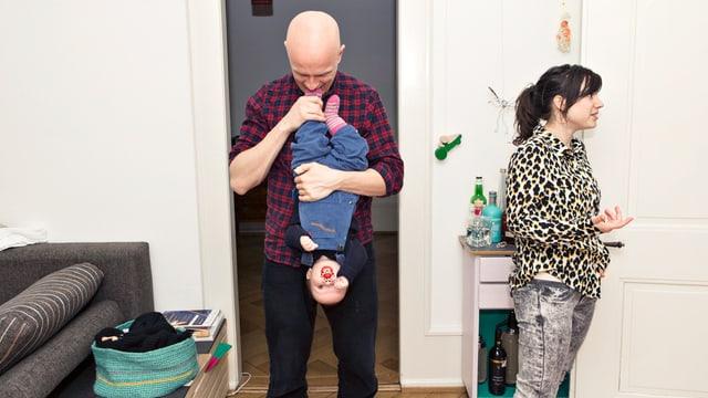 Mann spielt mit Kind und Frau redet mit jemandem