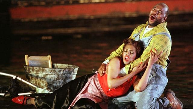 Ein schwarzer Mann und eine schwarze Frau umarmen sich auf einer Bühne.