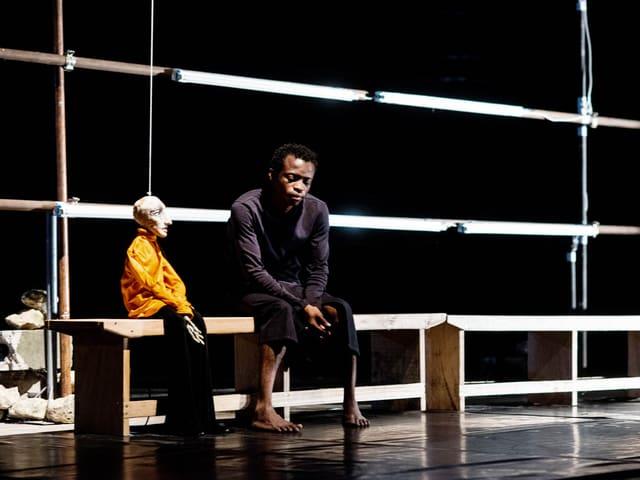 Bühnenszene: Linyekula sitzt auf einer Bank neben einer kleinen Holzpuppe.