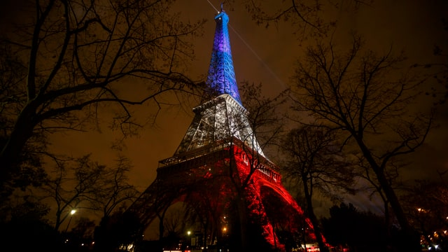 Eiffelturm nachts beleuchtet in blau, weiss, rot.
