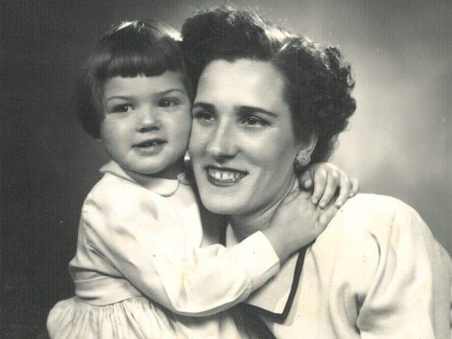Schwarz-Weiss-Fotografie mit einem kleinen Mädchen, das seine Mutter umarmt.