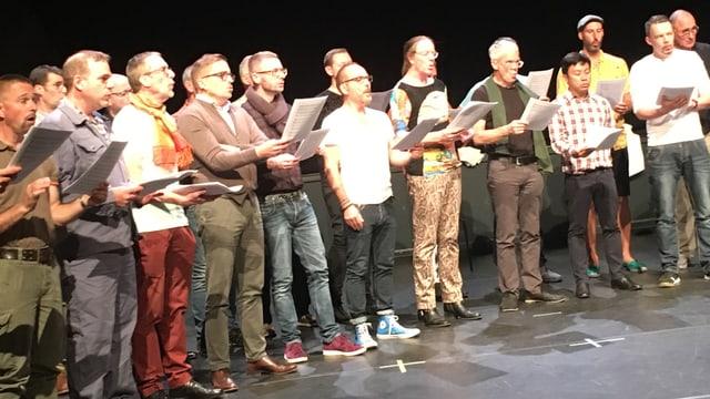 Männer stehen mit Musiknoten im Halbkreis und singen