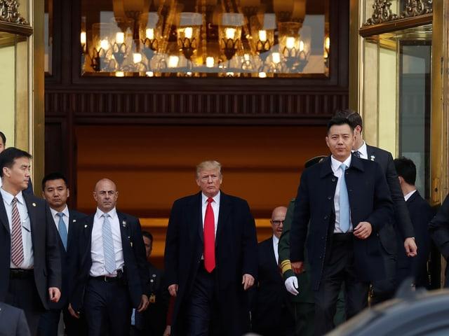 Trump geht mit Sicherheitsleuten aus Türe