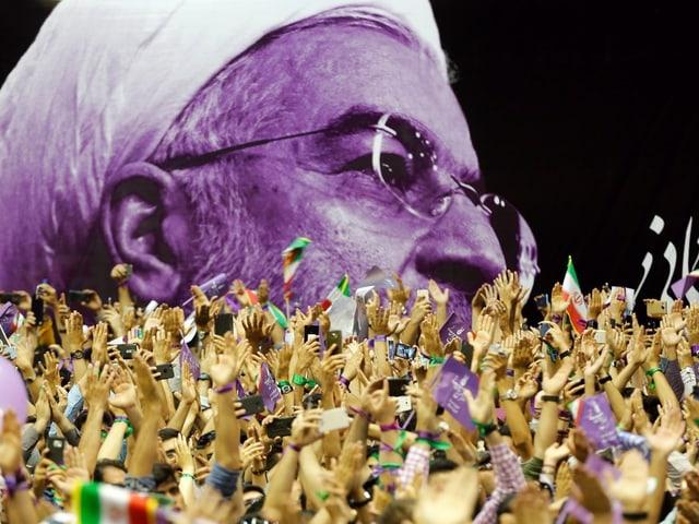 Zum Jubeln hoch gestreckte Hände vor einem übergrossen Plakat mit dem Kopf Rohanis drauf