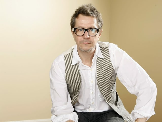 Ein Portrait von Gary. Er schaut direkt in die Kamera, trägt eine Brille, ein weisses Hemd und eine schwarz-weiss karierte Weste.