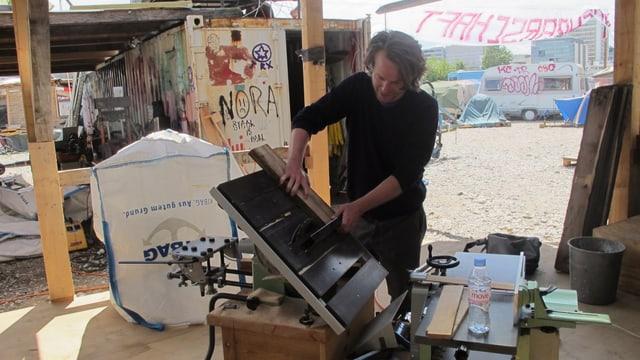 Werkstatt auf dem Wagenplatz. Ein Mann arbeitet an der Kreissäge, im Hintergrund sieht man den Kiesplatz.