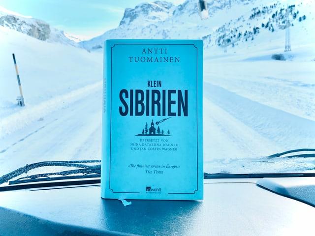 Der Krimi «Klein-Sibirien» von Antti Tuomainen ist vor die Windschutzscheibe eines Autos gehalten. Im Hintergrund sieht mein eine verschneite Strasse.