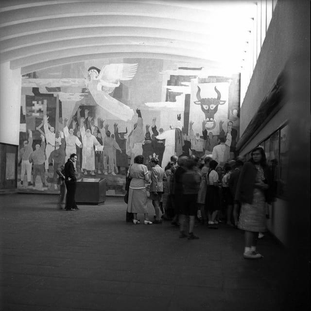 ein schwarz-weiss Foto von einem Saal, wo mehrere Leute versammelt sind