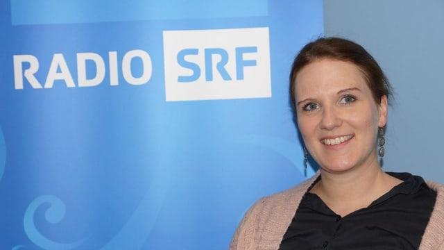 Lea Pfister-Scherer sitzt vor dem SRF Musikwelle Logo.