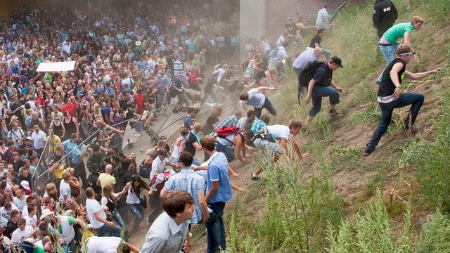 Menschenmasse, umkippender Zaun, fliehende Menschen
