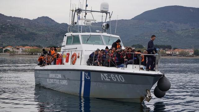 Kleinboot der griechischen Küstenwache mit Migranten in Schwimmwesten an Bord.