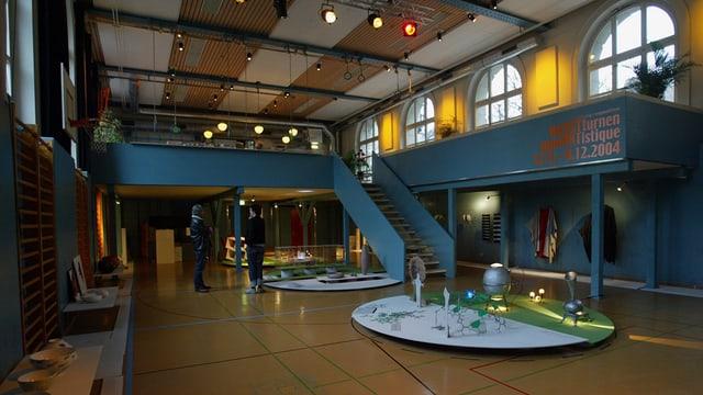 Das Innere des Progr Bern mit farbigen Treppen und Galerie und Bartischen.