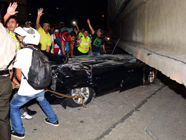 Menschen in Guayaquil versuchen ein eingeklemmtes Erdbebenopfer in einem Auto zu retten.