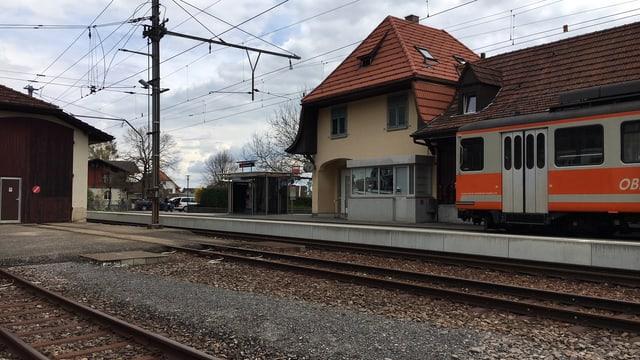 Bahnhofgebäude mit altem, orangem Zug auf einem Abstellgleis.