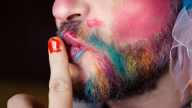 Ein Mann mit geschminktem Bart und roten Fingernägeln.