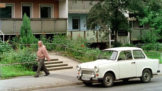 Ein Mann geht vor einem DDR-Plattenbau eine Strasse entlang. Am Strassenrand steht ein Trabant.