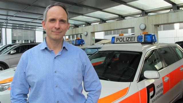 Mann in blauem Hemd vor Polizeiautos.