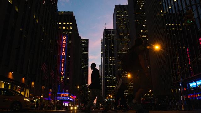 Ein Mann läuft in der Dämmerung zwischen Hochhäusern in New York.