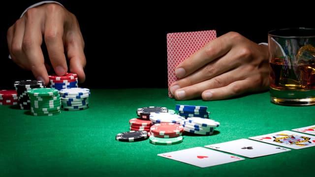 Poker-Tisch mit Chips; eine Hand im Dunkel hält Karten.