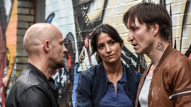 Drei Personen stehen vor einer besprayten Wand un spreche nmiteinander.