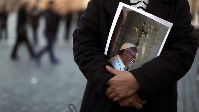 Mann mit Bild von Papst Franziskus in den Armen