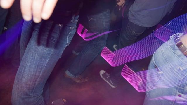Situaziun en in club, blera glieud stat dastrusch, illuminà da colur.