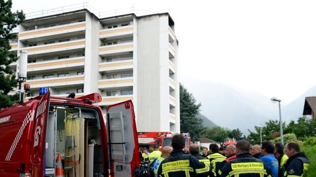 Feuerwehrleute stehen vor dem Hochhaus.