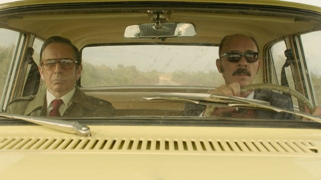 Zwei Männer sitzen im Auto.