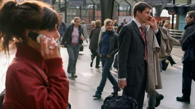 Aufnahme von zwei Personen, die an einem Bahnhof stehen und telefonieren.